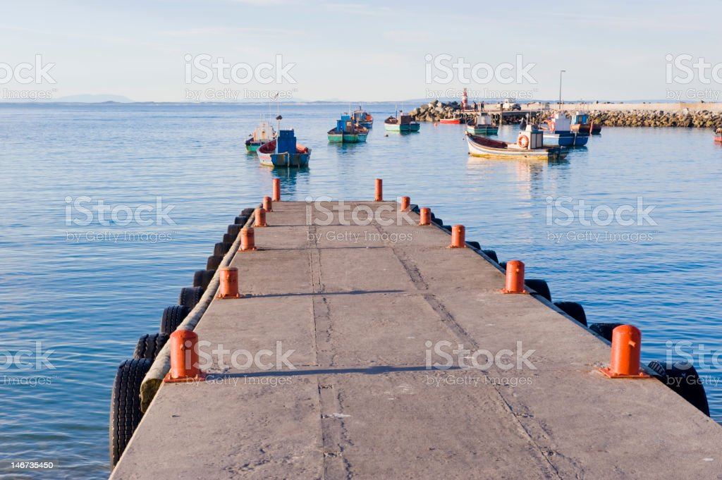 Jetty with fishing boats anchored in the distance royalty-free stock photo