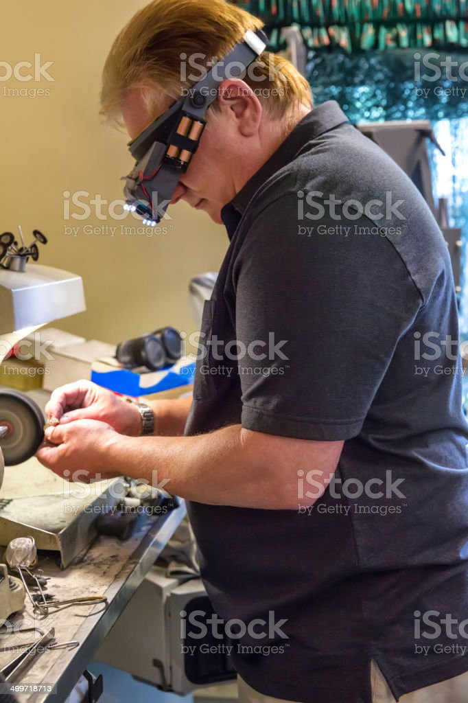 Jeweler at his workbench polishing a ring stock photo