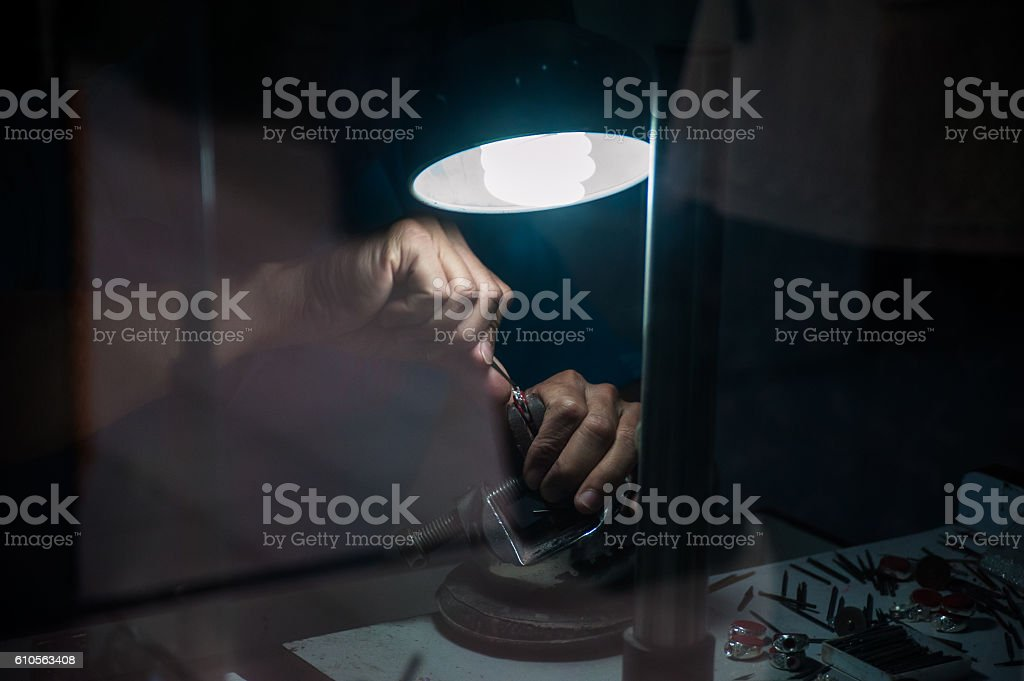 jeweler behind the glass. Work with jewelry stock photo