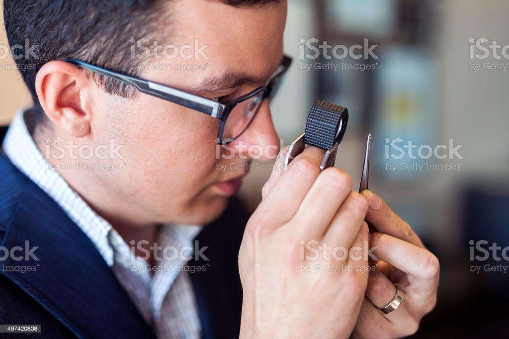 Jeweler examining diamond through loupe stock photo