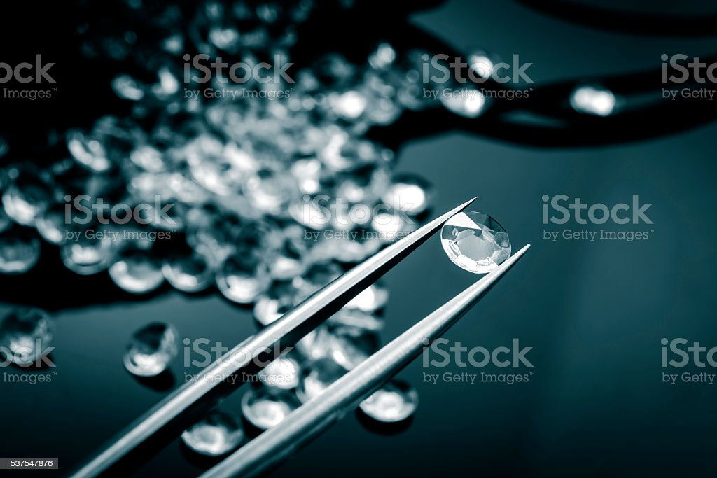 Jeweler inspecting a diamond with tweezers stock photo