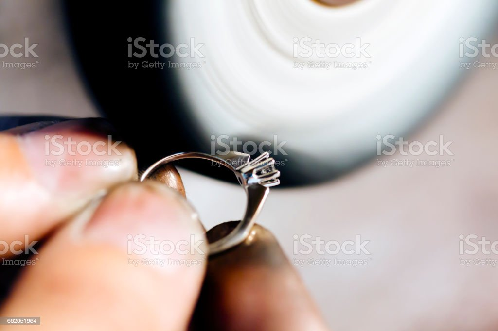 Jeweler polishing jewelry with tools stock photo