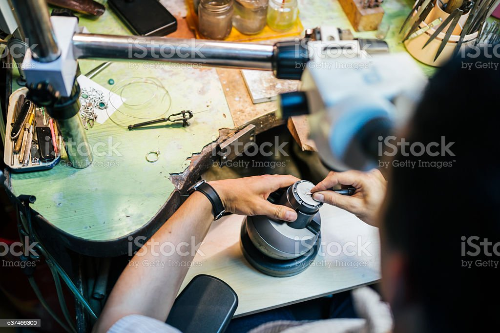 Jeweler working with optical device stock photo