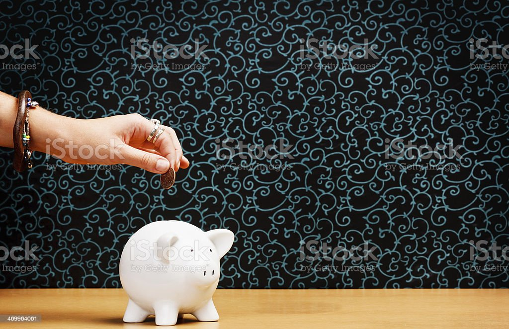 Jewelled hand drops coin into piggybank royalty-free stock photo