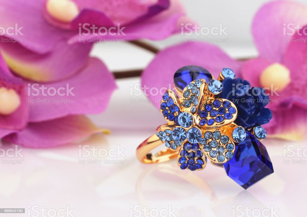 Jewellery ring with blue gems and flower Archidea background stock photo