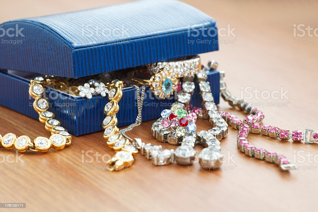 A jewelry box with jewelry overflowing on a wooden table royalty-free stock photo