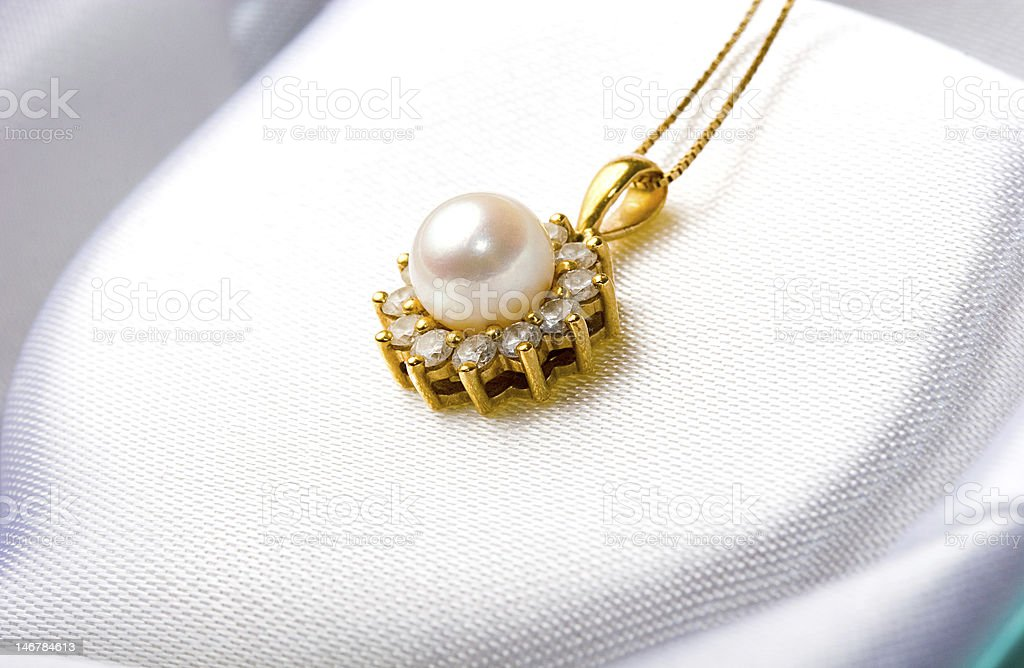 Jewelry gold pearl pendant with diamonds inside a gift box stock photo