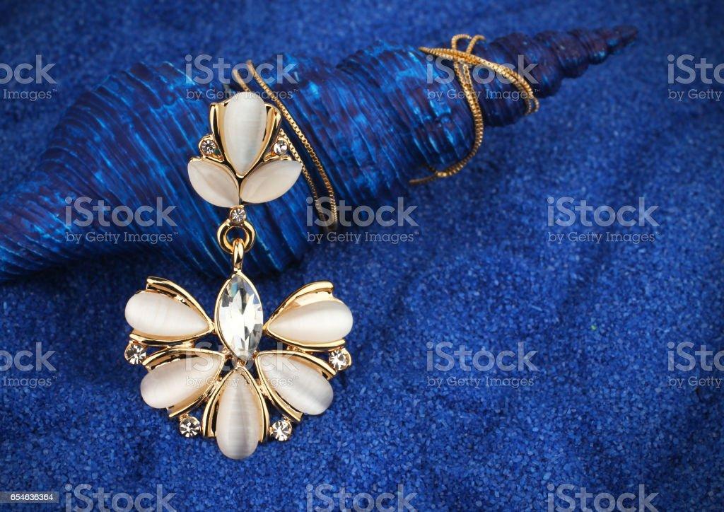 Jewelry pendant with nacre and diamonds on blue seashell background stock photo