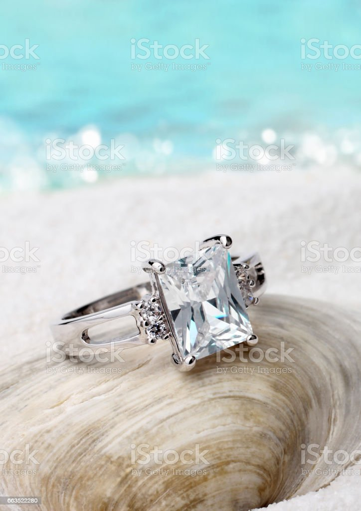 Jewelry ring with diamond on sand beach background, soft focus stock photo