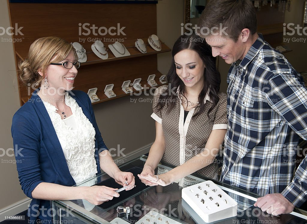 Jewelry store employee helping engaged couple stock photo