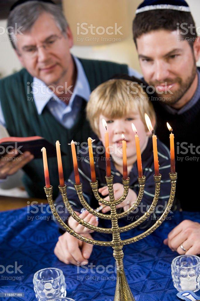 Jewish family lighting Chanukah menorah royalty-free stock photo