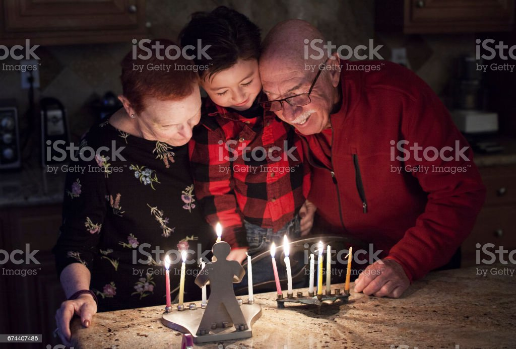 Jewish Family with granparents and grandson lighting Hanukkah Candles in a menorah for the holidays stock photo