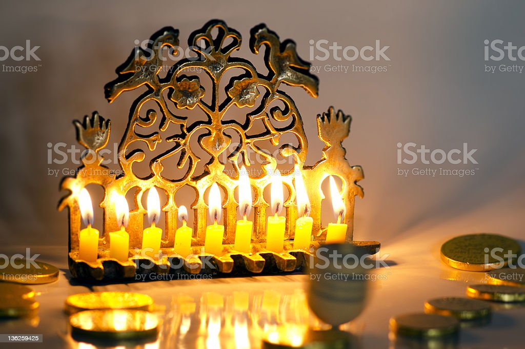 Photo of a dreidel , gelts and an ancient brass menorah for the...