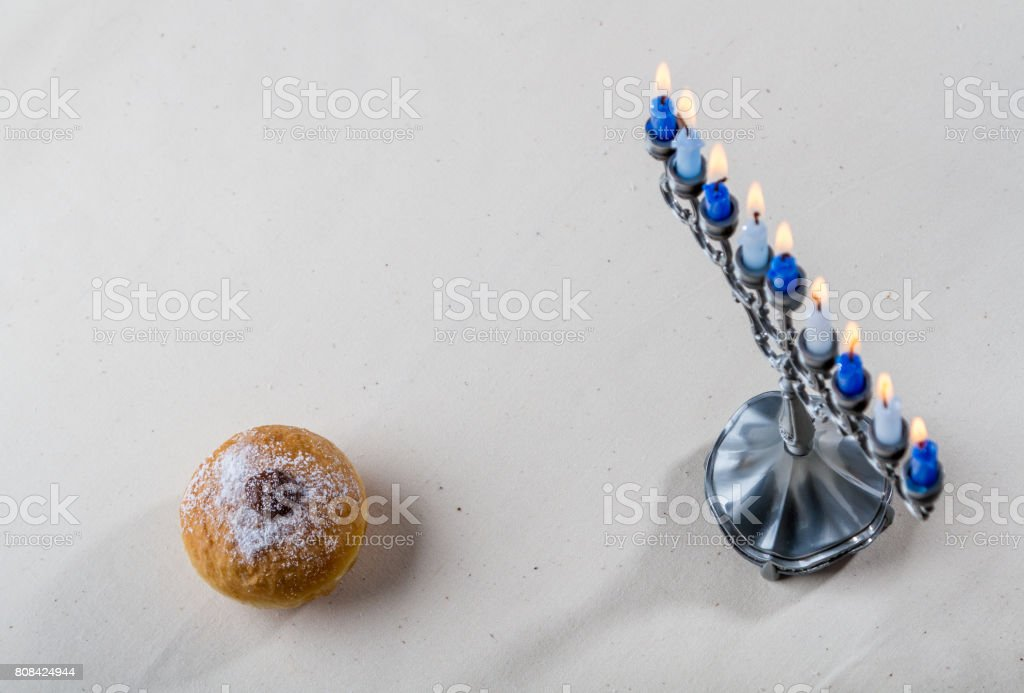 Jewish holiday of Hanukkah, hanukkah menorah and sufganiyah stock photo