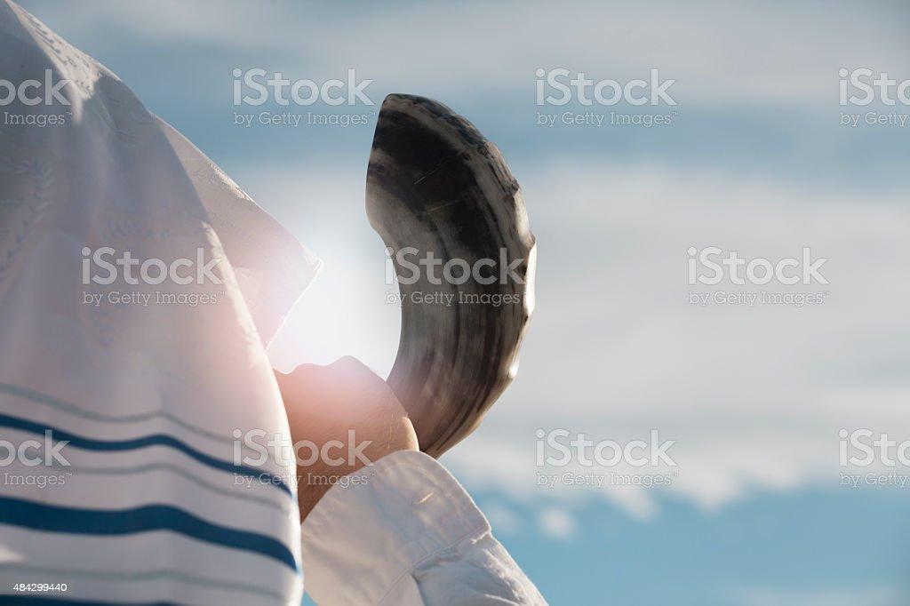 Jewish man blowing the Shofar against blue sky stock photo