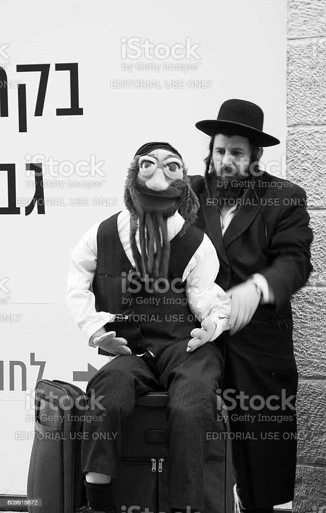 Jewish ultra-orthodox man performing with his puppet. stock photo