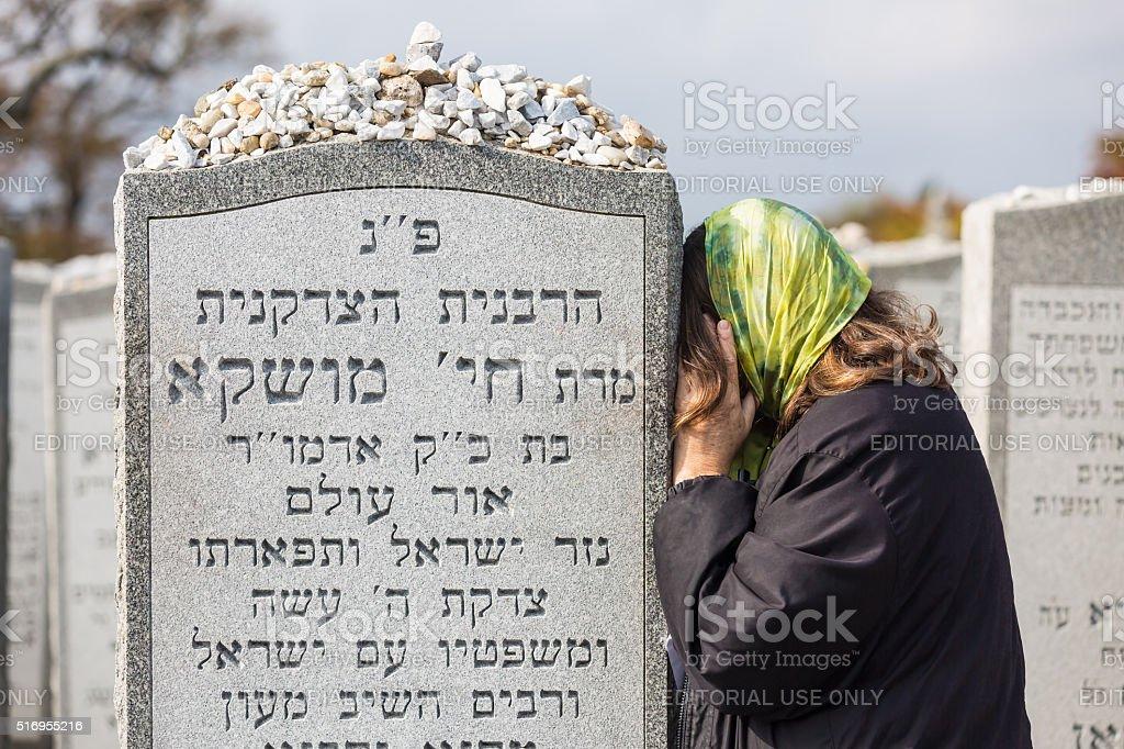 Jewish woman prays at graveside of Rebbetzin Chaya Mushka stock photo