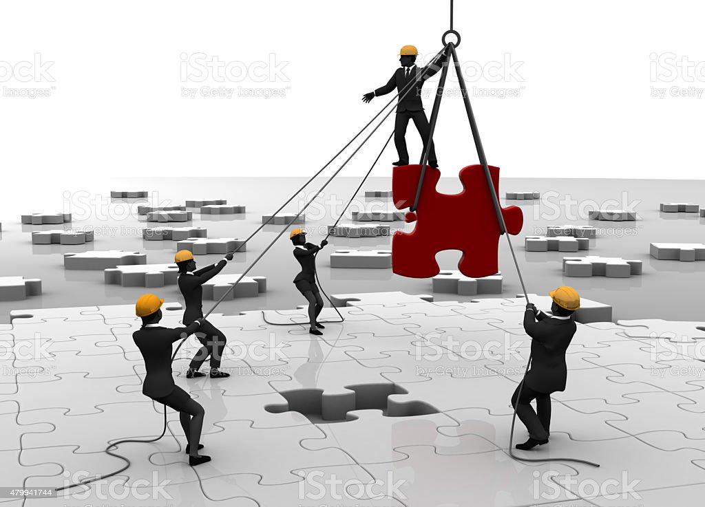 Jigsaw puzzle being built by teamwork stock photo