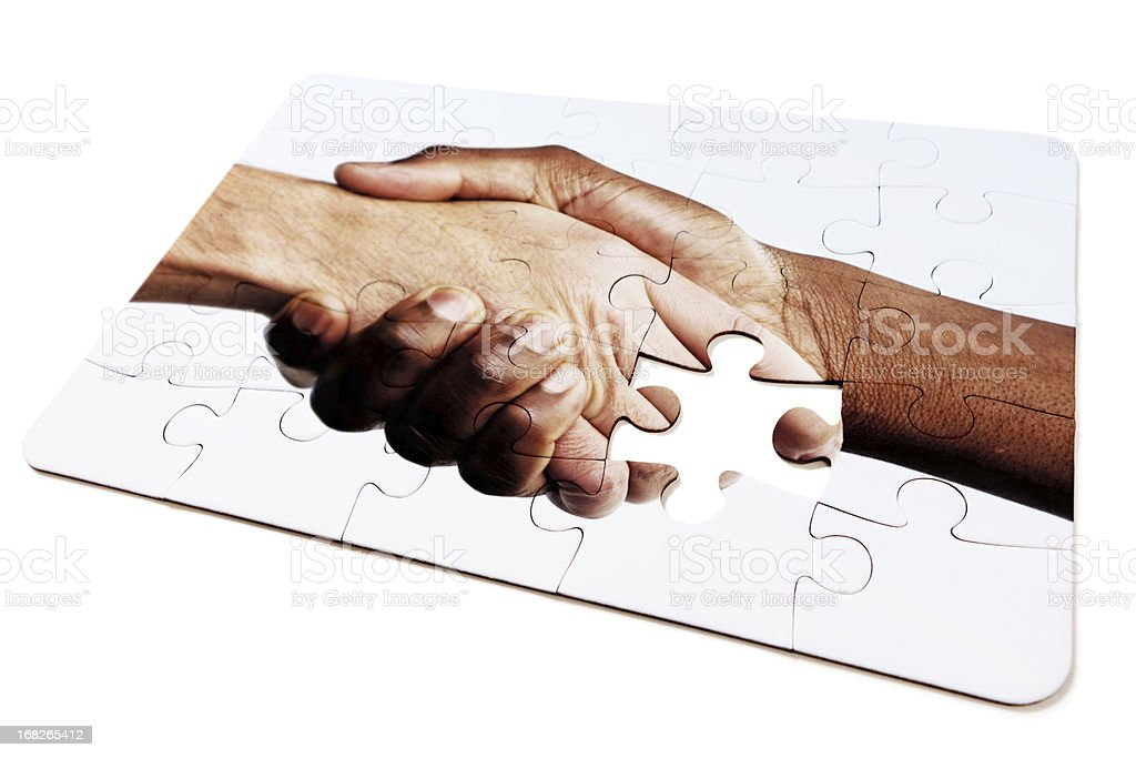 Jigsaw puzzle design of interracial handshake, with one piece missing royalty-free stock photo