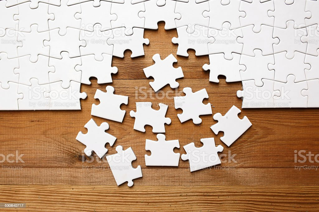 Jigsaw puzzle on wood stock photo