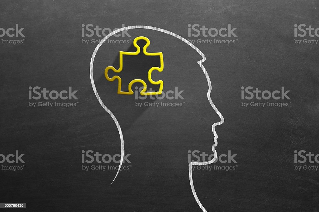 Jigsaw puzzle piece drawn on black board in man head stock photo