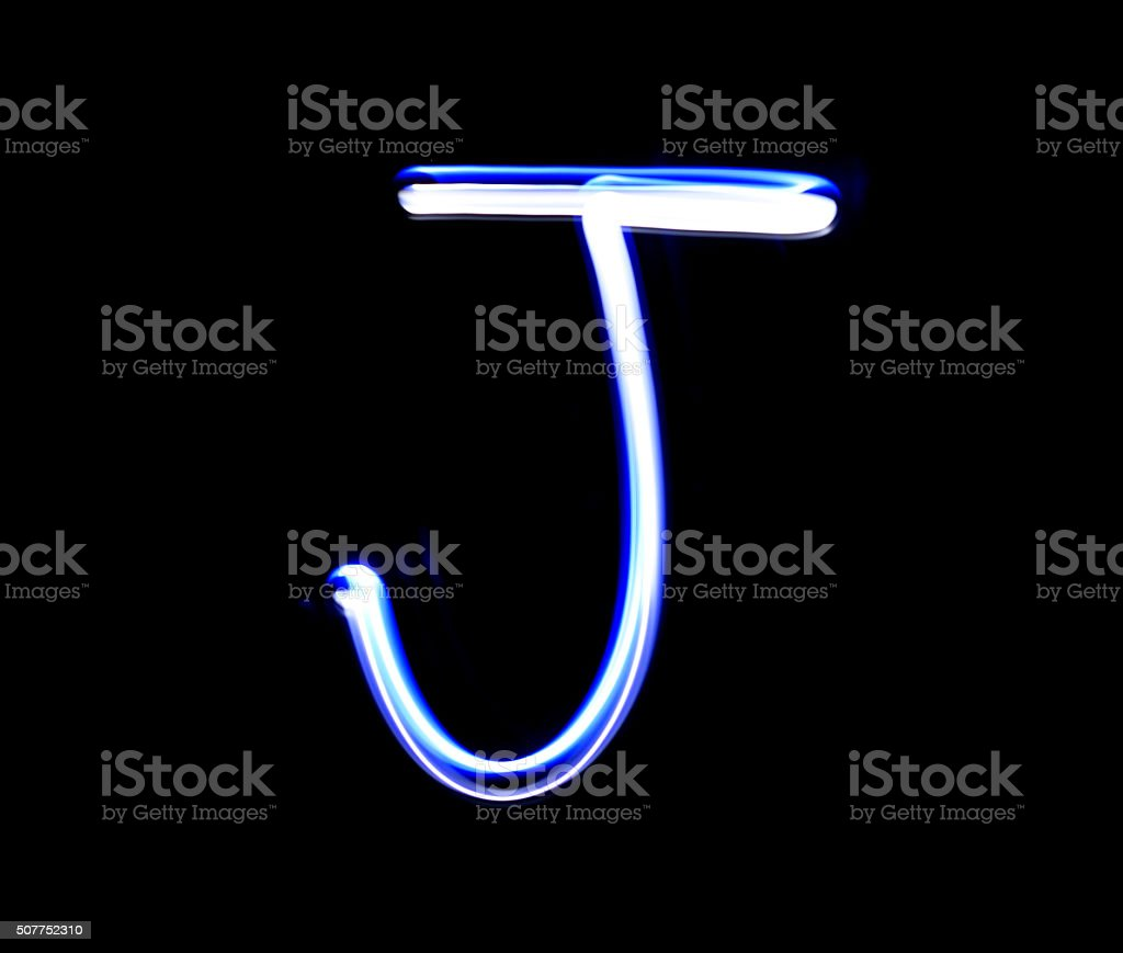 J Jimmy alphabet hand writing blue light  over black background. stock photo