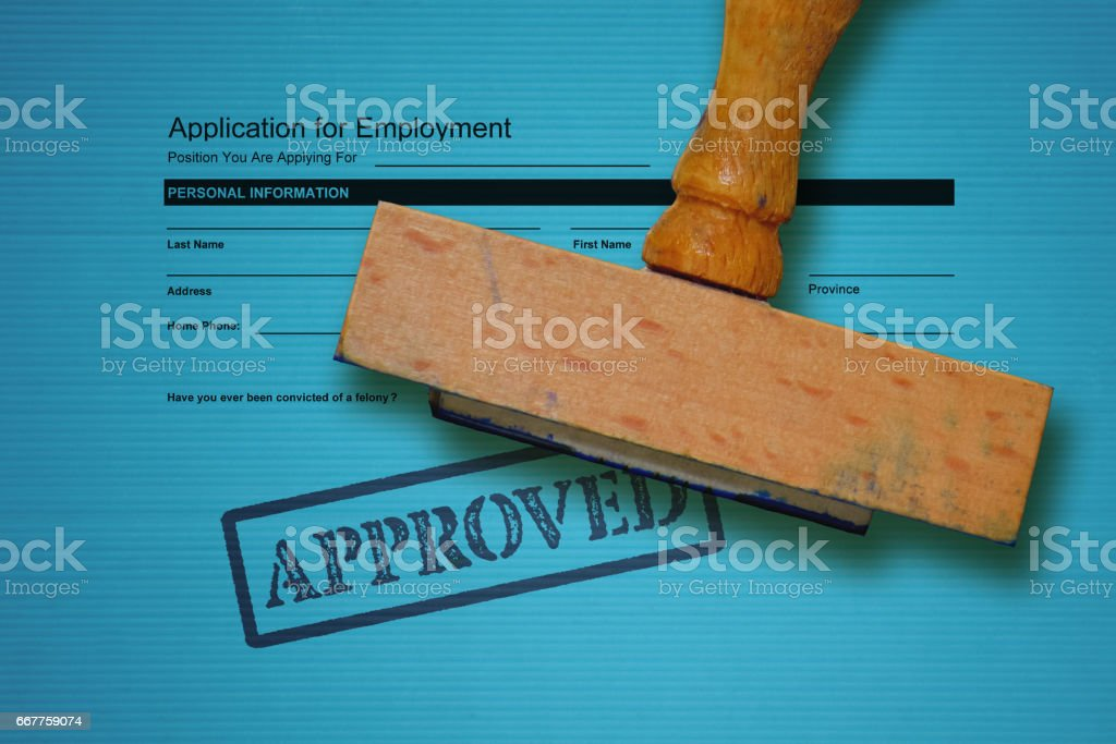 Job application form and wooden stamp on blue background stock photo
