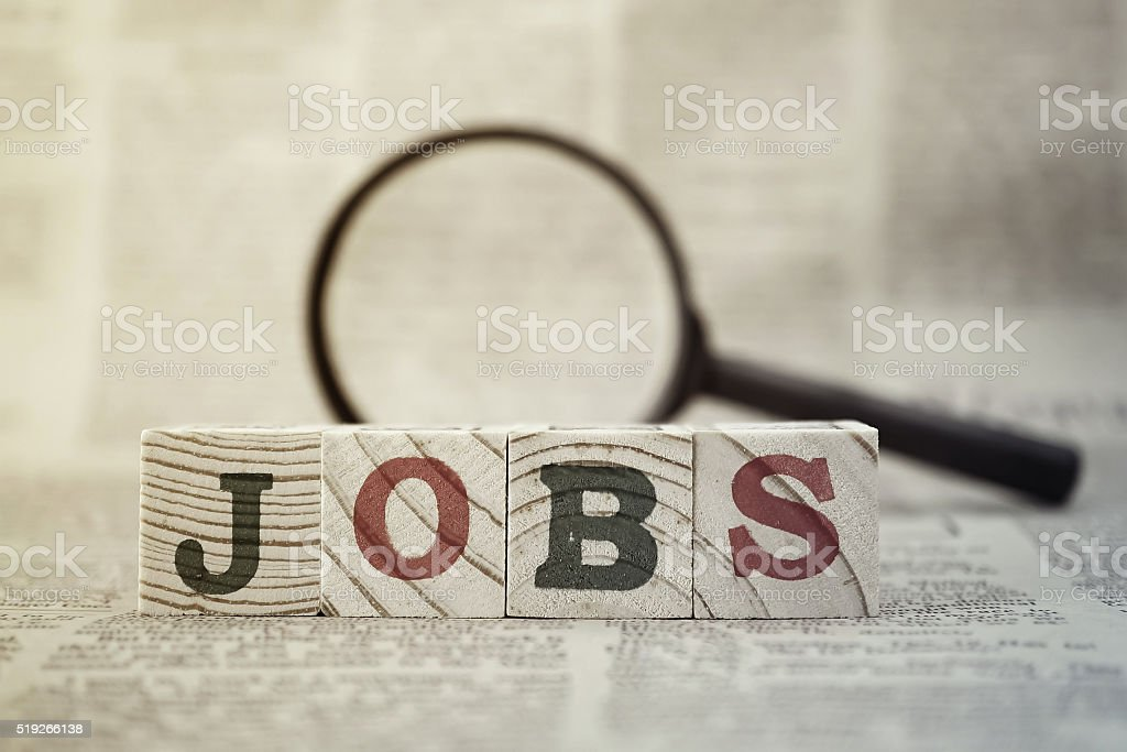 'Jobs' on wooden block and magnifying glass on newspaper background stock photo