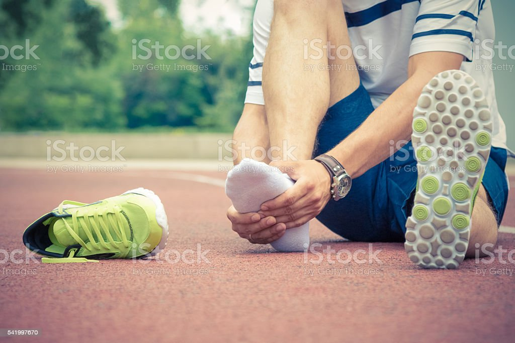 Jogger checking if his ankle is broken or twisted stock photo