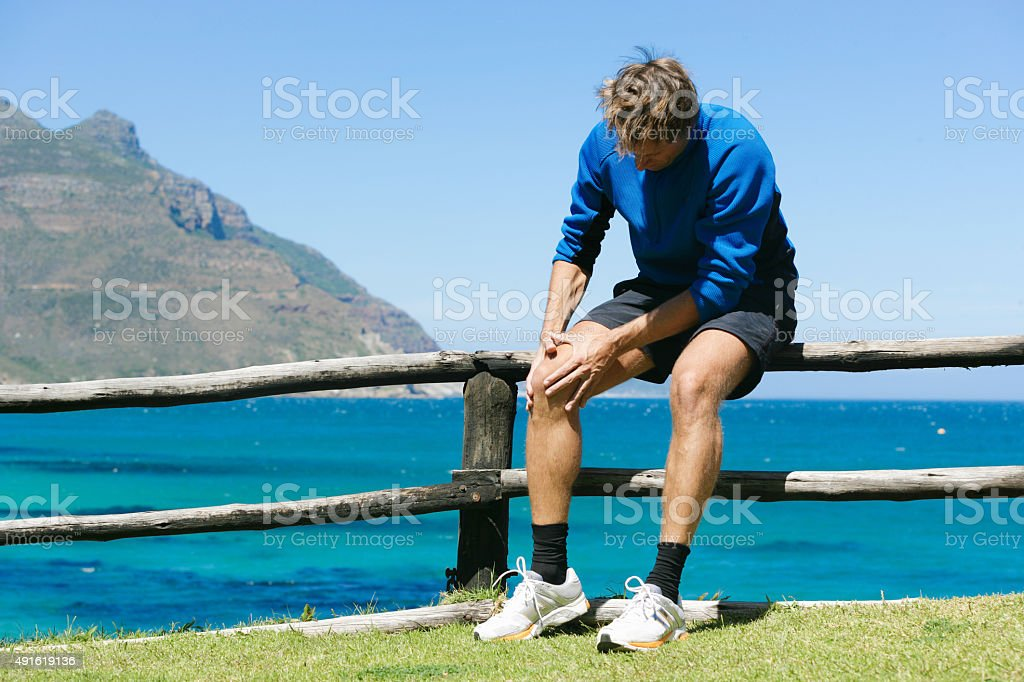 Jogger having severe knee pain in stunning surrounding of Southafrica stock photo