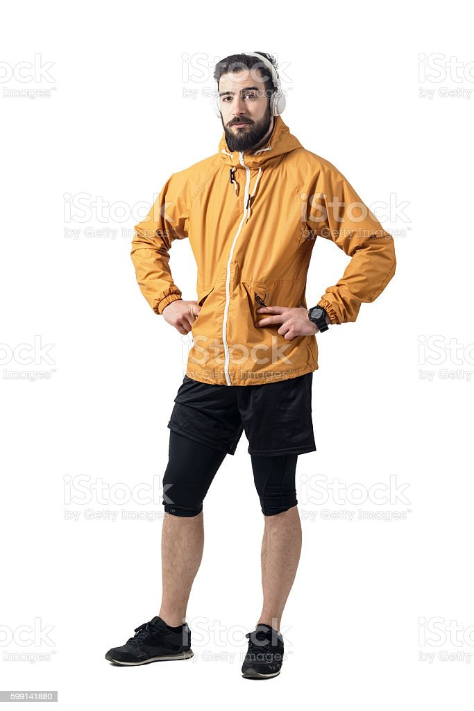 Jogger in sports jacket with earphones looking at camera stock photo