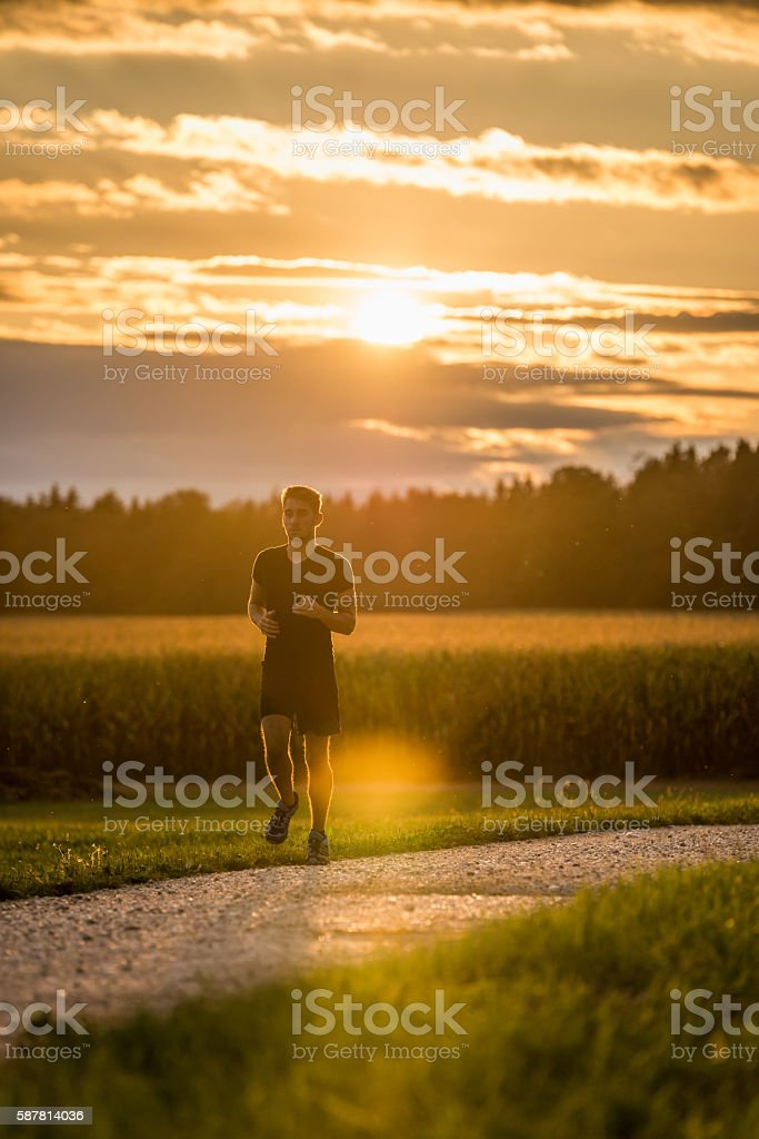 jogger in sunset stock photo