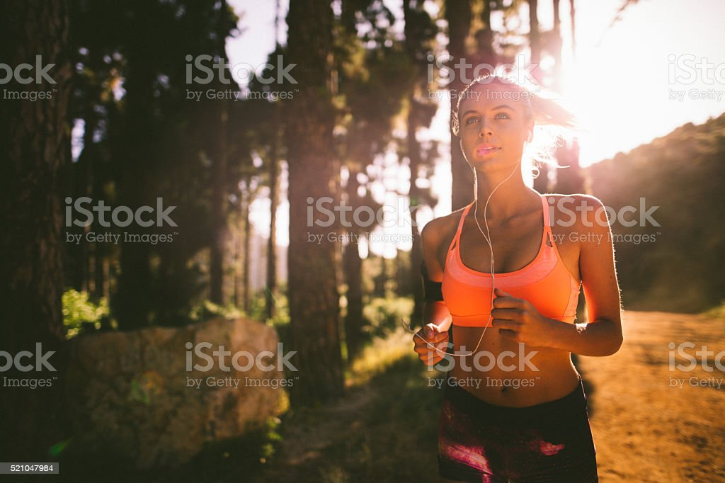 Jogger listening to earphones on a morning mountain running trai stock photo