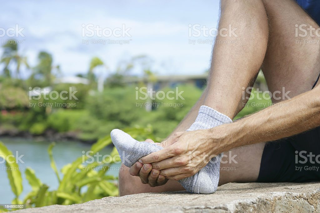Jogger massaging the metatarsal area of the foot stock photo