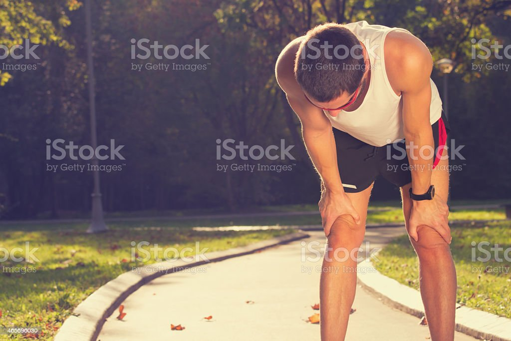A jogger resting on while checking the running time stock photo