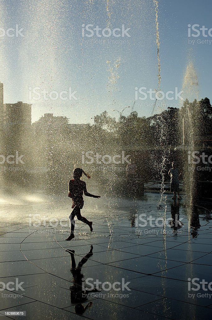 A jogger running through a water feature royalty-free stock photo