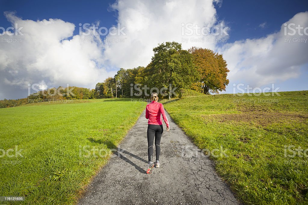 Jogger Running Uphill on path in Green Fields royalty-free stock photo
