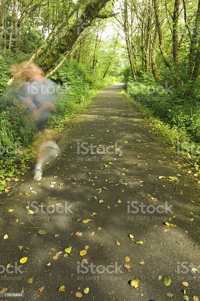 Jogger runs on a foot path through the forest royalty-free stock photo