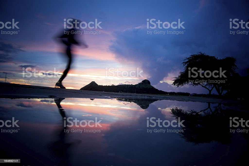 jogger silhouette and reflection against colorful sunset sky stock photo