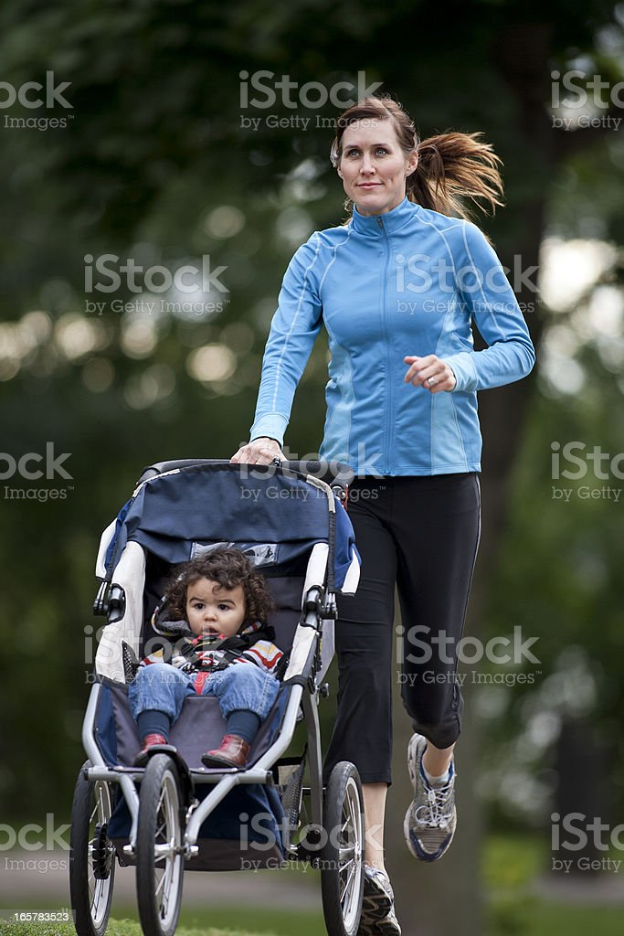 Jogger With Baby Jogger Running On a Paved Trail. stock photo