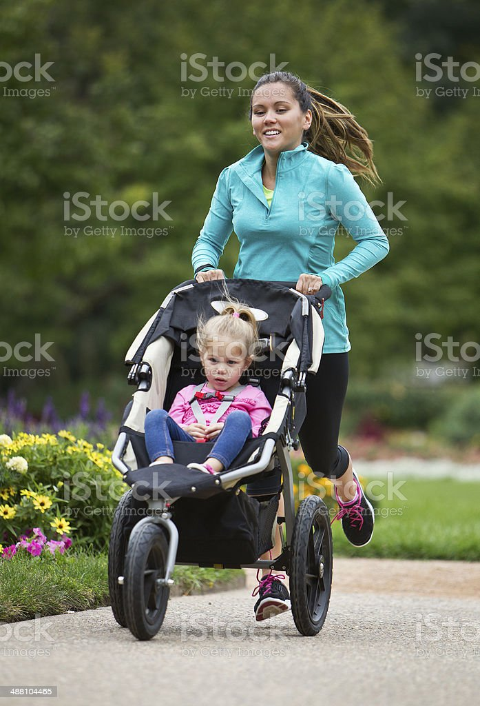 Jogger With Baby Jogger Running on Paved Trail. stock photo