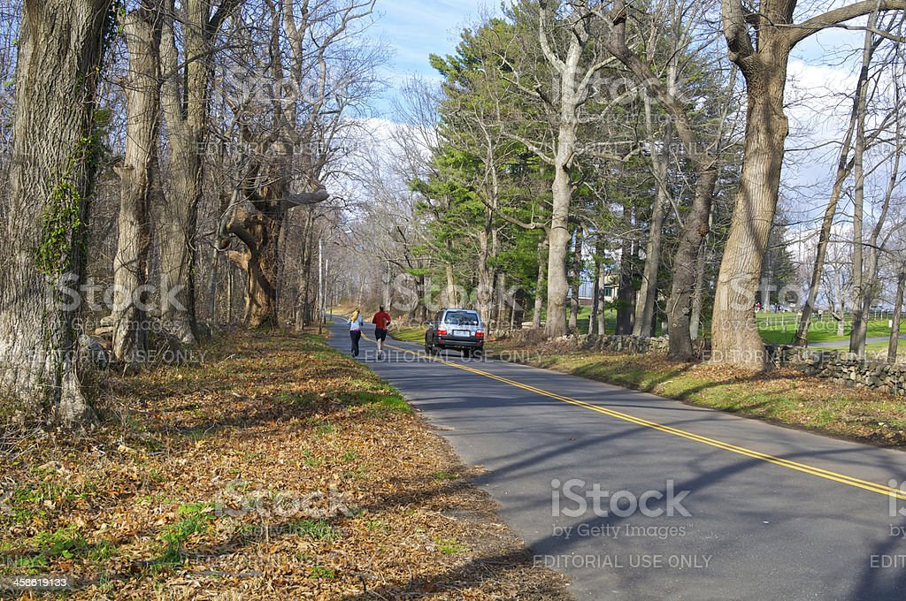Joggers and automobile on a suburban road, Connecticut, USA stock photo