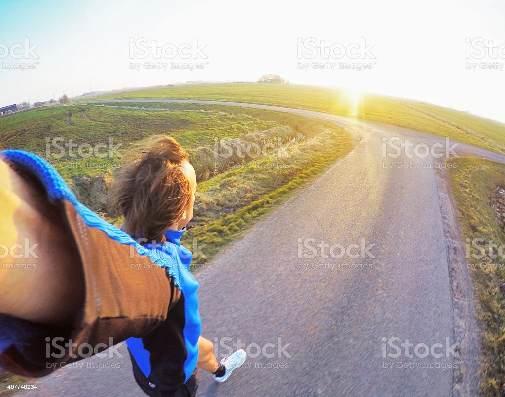 Jogging at sunset on tarr road towards intersection, GoPro image stock photo