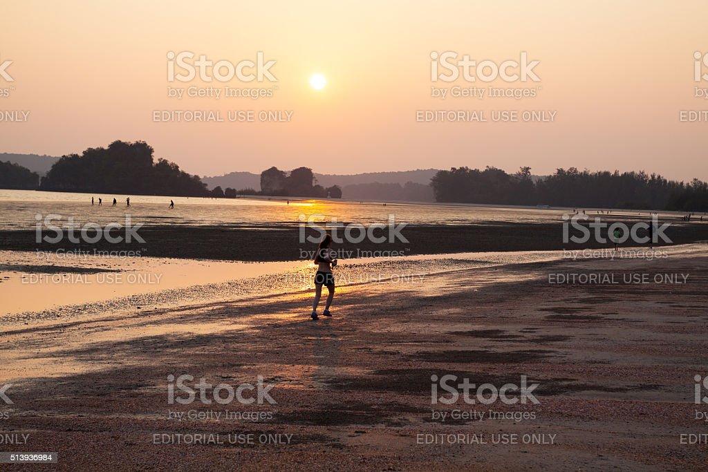 Jogging female tourist on beach at sunset stock photo