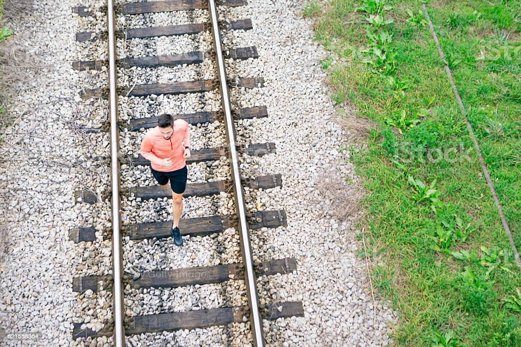 Jogging on railroad tracks stock photo