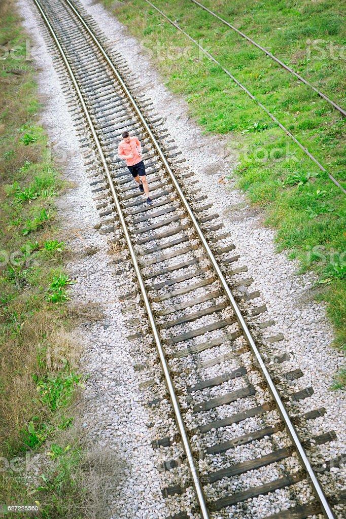 Jogging on railroad tracks stock photo