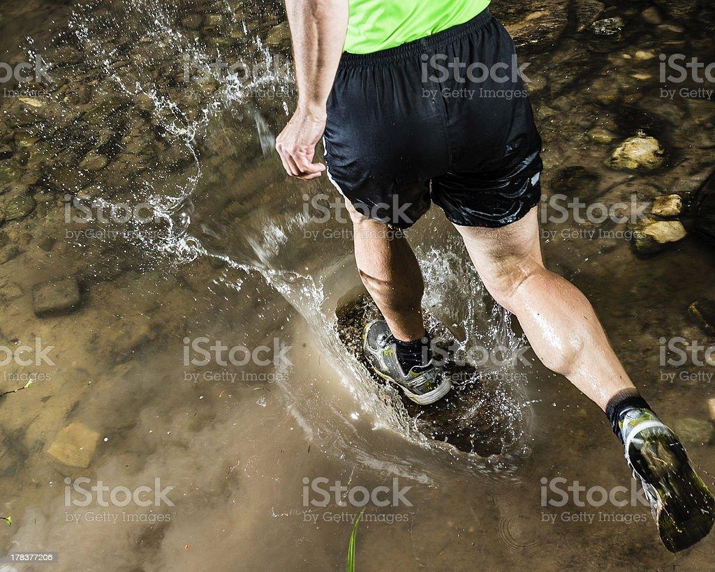 jogging throug a streambed royalty-free stock photo