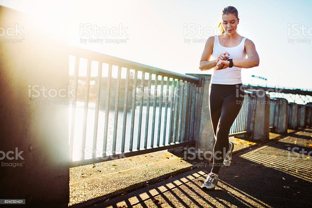 Jogging Woman Checks Smart Watch stock photo