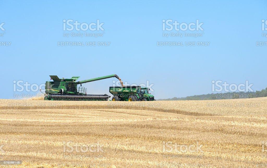 John Deere Combine Harvesting Wheat stock photo