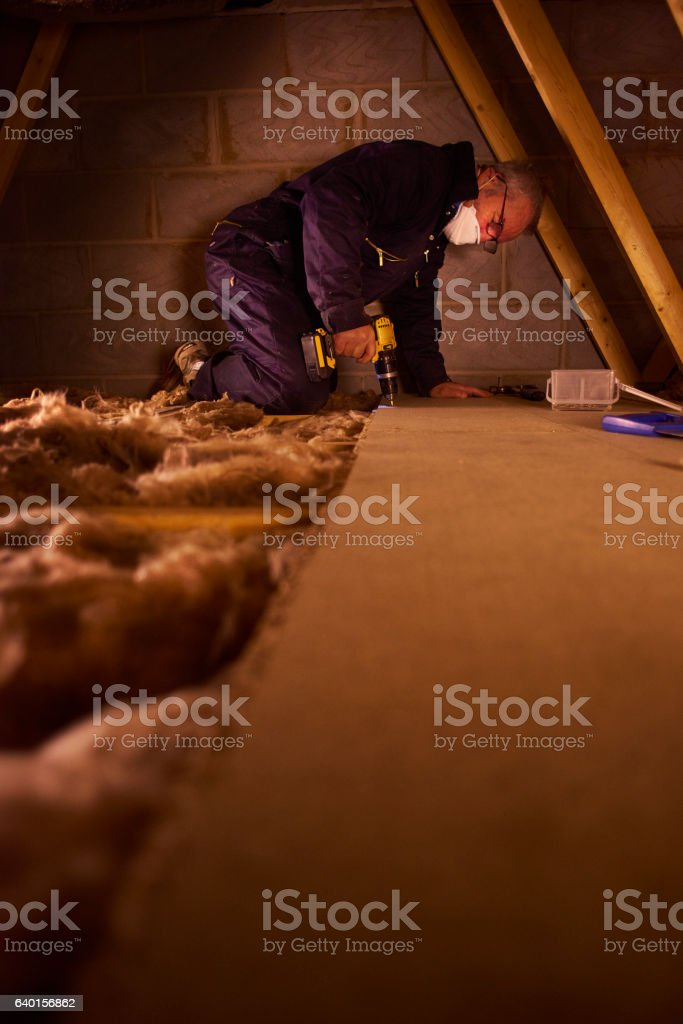joiner laying attic floorboards stock photo